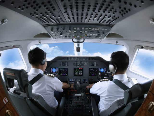 26391543 - pilot and co-pilot in private jet cockpit